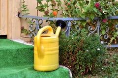 Żółty wodnego wiadra dzbanek umieszczający na kamieni krokach przed chałupy drzwi Zdjęcia Royalty Free