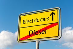 Żółty znak uliczny z elektrycznymi samochodami naprzód opuszcza dieslowskiego behin fotografia stock