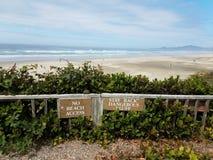 Żadny plażowy dostępu pobytu z powrotem blefu niebezpieczny znak na płotowej pobliskiej plaży z piaskiem i falami zdjęcie royalty free