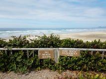Żadny plażowy dostępu pobytu z powrotem blefu niebezpieczny znak na płotowej pobliskiej plaży z piaskiem i falami fotografia royalty free