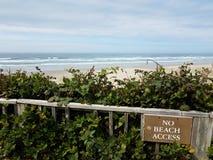 Żadny plażowy dostępu znak na płotowej pobliskiej plaży z piaskiem i falami obraz stock