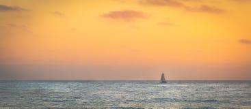 Żaglówka żegluje przez horyzont rozjarzony niebo i morze obrazy stock