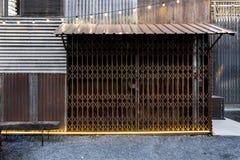 Żaluzja metalu toczny drzwiowy ośniedziały na starej cynku i drewna ścianie zdjęcie stock