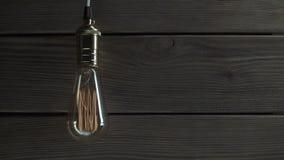 Żarówka iluminuje na drewnianym tle zbiory wideo