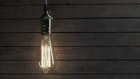 Żarówka iluminuje na drewnianym tle zbiory