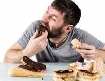 Żarłoka mężczyzna łasowania brodate babeczki z szaleństwem po długiej diety obraz royalty free
