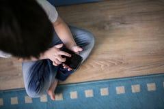 Żartuje chłopiec bawić się z mądrze telefonem, kopii przestrzeń, real Zdjęcia Stock