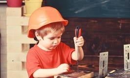 Żartuje chłopiec w pomarańczowym ciężkim kapeluszu lub hełmie, nauka pokoju tło Chłopiec sztuka jako budowniczy lub naprawiacz, p obrazy royalty free