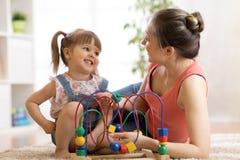 Żartuje dziewczyn sztuki z edukacyjną zabawką w pepinierze w domu Szczęśliwy macierzysty patrzejący jej mądrze córki zdjęcie royalty free