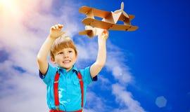 Żartuje fantazję Dziecko bawić się z zabawkarskim samolotem przeciw niebu i cl Fotografia Stock