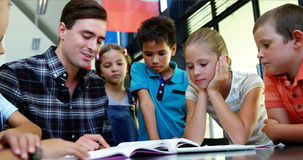 Żartuje słuchanie nauczyciel podczas gdy czytelnicza książka w sala lekcyjnej zbiory