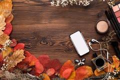 Żeńscy akcesoria Ustawiający jesień liście, smartphone i słuchawki na drewnianym tle, obrazy stock