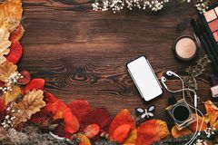 Żeńscy akcesoria Ustawiający jesień liście, smartphone i słuchawki na drewnianym tle, fotografia royalty free