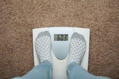 Żeńscy cieki w skarpetach na elektronicznych skalach Nadmierny ciężar i dieta obraz royalty free