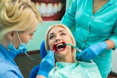 Żeńscy dentyści taktuje cierpliwych dziewczyna zęby Młody blondynki dziewczyny sittiong przy dentystą Fotografia Stock