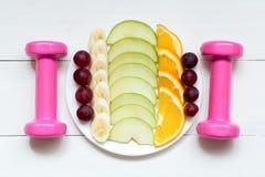 Żeńscy dumbbells i owoc na białym talerzu na białym drewnianym tle zdjęcie stock