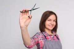 Żeńscy fryzjera mienia nożyce przy szarym tłem fotografia royalty free