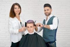 Żeńscy i męscy hairstylists robi ostrzyżeniu dla młodego klienta z stonowanym włosy zdjęcie stock