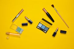 Żeńscy kosmetyki dla makijażu układu na żółtym tle Kosmetyk ocienia, makijażu muśnięcie, eyeshadow pomadka, pachnidło butelka fotografia stock