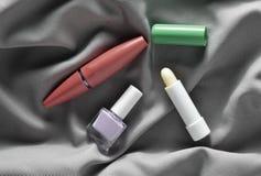 Żeńscy kosmetyki: tusz do rzęs dla oczu, gwoździa połysk, higieniczna pomadka na szarej jedwabniczej tkaninie, odgórny widok obrazy stock