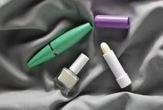 Żeńscy kosmetyki: tusz do rzęs dla oczu, gwoździa połysk, higieniczna pomadka na szarej jedwabniczej tkaninie, odgórny widok obraz stock