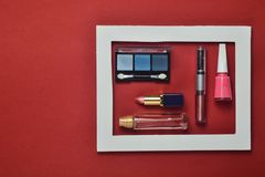 Żeńscy kosmetyki w białej ramie na czerwonym tle Cienie dla makijażu, pomadka, gwoździa połysk, pachnidło butelka obraz stock