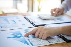 Żeńscy księgowych obliczenia i analizować pieniężnego wykresu data Obraz Stock