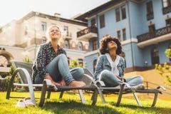 Żeńscy przyjaciele plenerowi na daybeds cieszy się jesieni światło słoneczne Zdjęcie Stock