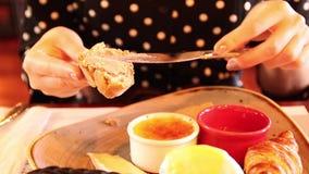 Żeńscy ręka chwyty wewnątrz wręczają świeżego kawałek chleb i rozmazy ja z łbem ?niadanie w kawiarni Stół z różnorodnymi typami n zdjęcie wideo