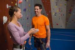 Żeńska atleta opowiada męski trener przy zdrowie klubem Fotografia Stock