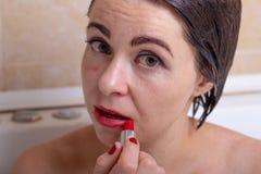 Żeńska depresja kobieta w łazience z osłupiałym spojrzeniem sieka pomadkę na jej twarzy zdjęcie stock