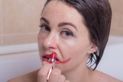 Żeńska depresja kobieta w łazience z osłupiałym spojrzeniem sieka pomadkę na jej twarzy obrazy royalty free