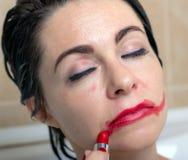 Żeńska depresja kobieta w łazience z osłupiałym spojrzeniem sieka pomadkę na jej twarzy obraz stock