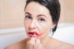 Żeńska depresja kobieta w łazience z osłupiałym spojrzeniem sieka pomadkę na jej twarzy fotografia stock