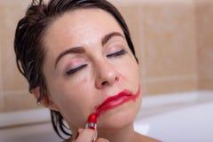 Żeńska depresja kobieta w łazience z osłupiałym spojrzeniem sieka pomadkę na jej twarzy obraz royalty free