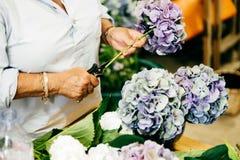 Żeńska kwiaciarnia robi pięknym bouquetes podczas gdy stojący przy kwiatu sklepem Unrecognizable osoba tworzy bouquetes cudowny f obrazy royalty free