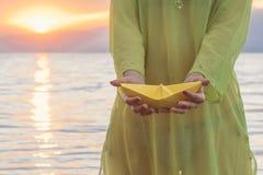 Żeńska mienie papieru łódź na plaży przy zmierzchem obraz royalty free
