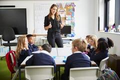 Żeńska nauczyciel pozycja w sali lekcyjnej gestykuluje ucznie, siedzi przy stołowym słuchaniem zdjęcie royalty free