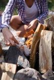 Żeńska obozowicz rozpałka zaczynać ognisko, ogniska zakończenie Mężczyzna rozognia ogienia Ogień w naturze Ognisko w lesie Zdjęcie Royalty Free