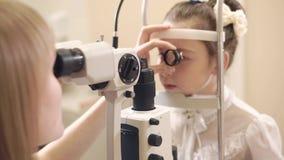 Żeńska oko lekarka sprawdza małej dziewczynki w biurze, używać biomicroscopy metodę zbiory