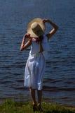 Żeńska osoba w bielu kapeluszu na brzeg rzeki i sukni Zdjęcie Royalty Free