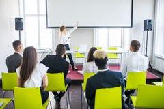 Żeńska pracownik podwyżki ręka pyta pytanie bizneswoman robi flipchart prezentacji Młodej kobiety odpowiadanie podczas zdjęcie stock