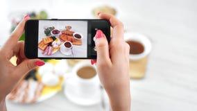 Żeńska ręka bierze fotografię apetyczny śniadanie na stołowym używa smartphone POV strzale zbiory wideo