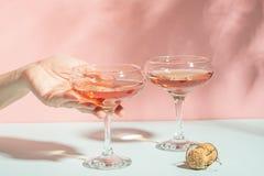 Żeńska ręka elegancko trzyma szkło szampana lub wina delikatnego różowego tła jaskrawy światło słoneczne Poj?cie minimalizm zdjęcia royalty free