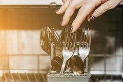 Żeńska ręka kłaść naczynia w otwartym zmywarkim do naczyń w górę zapchanego z czystymi, myjącymi naczyniami, suchy cutlery zbli?e zdjęcia royalty free