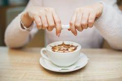 Żeńska ręka nalewa cukier w kawę Drewniany Stołowy tło zdjęcie royalty free