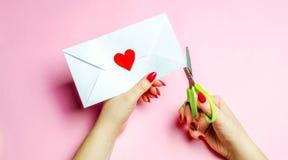 Żeńska ręka otwiera kopertę z czerwonym sercem List miłosny ukochany tła błękitny pudełka pojęcia konceptualny dzień prezenta ser zdjęcie stock