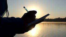 Żeńska ręka pisze puszkowi coś w ochraniaczu przy zmierzchem w 4k zbiory wideo