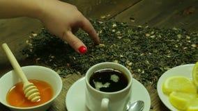 Żeńska ręka pisze słowo herbacie na herbacianych liściach rozpraszających na drewnianym stole zbiory
