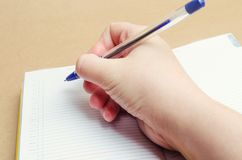 Żeńska ręka pisze w notatniku i robi notatkom, plany dla dnia, lista zakupów, zakończenie, biznesmen robi notatkom na cal Fotografia Stock